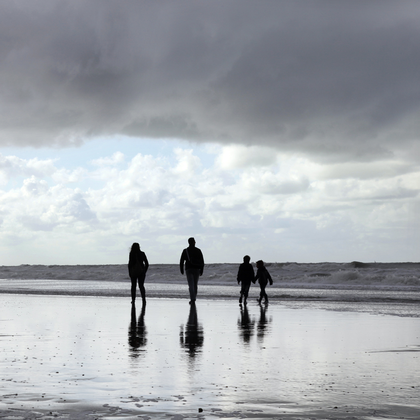 Gezin in silhouet aan het strand