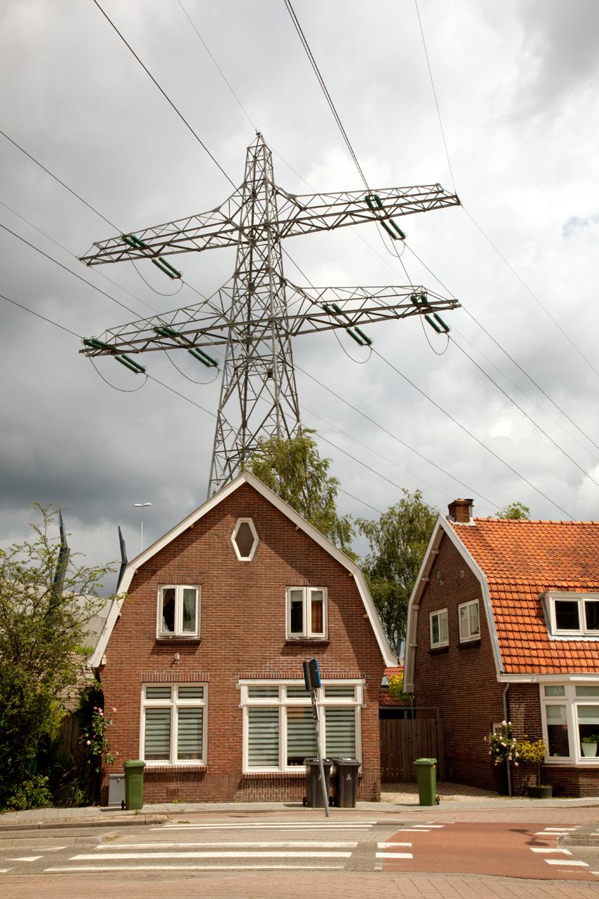 Klein huis met hoogspanningsmast